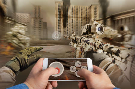 First person view photo of a male hand in jeans shirt holding smartphone and playing war battlefield shooter game. Stockfoto