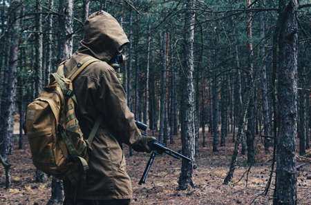 Photo of a nuclear war stalker soldier standing and posing in soviet gas mask, backpack with rifle in woods back view.