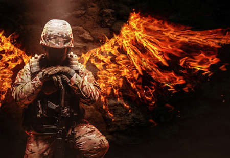 Photo of a fully equipped military soldier in helmet, armor vest and rifle kneeling with fire wings behind him. Standard-Bild