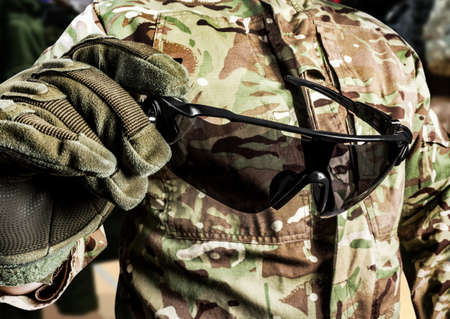Photo of soldier in military multicam shirt and gloves holding tactical glasses side view. Stockfoto