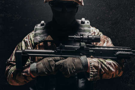 Photo of a fully equipped shaded military soldier in helmet, armor vest holding sniper rifle on dark background. Stockfoto