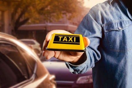 Photo of male hand in shirt holding taxi sign on evening car parking lot. Stockfoto