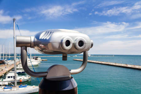 Coin operated binocular viewing machine on sea yacht port. Stockfoto