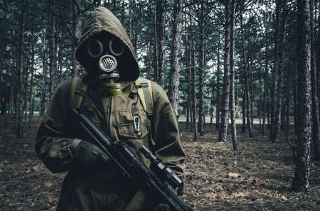 Photo of a nuclear war stalker soldier standing and posing in soviet gas mask, backpack with rifle in woods.