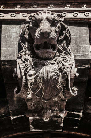 Photo of a stone lion statue bas-relief on building.