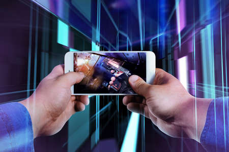 First person view photo of a male hand in jeans shirt holding smartphone and playing futuristic shooter game on neon evirontment background.