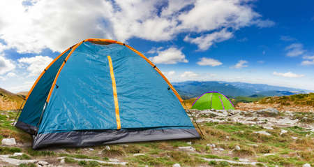Photo of a sunny day camping tents standing on a peak of a mountain.