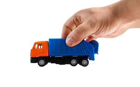 Isolated photo of a male hand holding a toy garbage truck on white background. Stockfoto