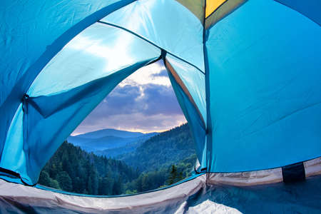Photo of early morning mountains valley view from a blue camping tent door.