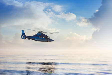 Passanger travel helicopter flying over evening sea with cloudscape.