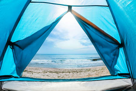 Photo of a sunny day sea shore view from a blue camping tent door.