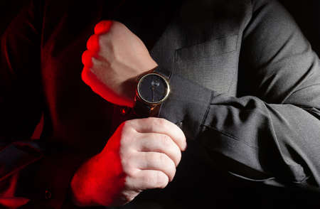 Photo of a male arms in black shirt and vest putting on elegant watch on black background. Stockfoto