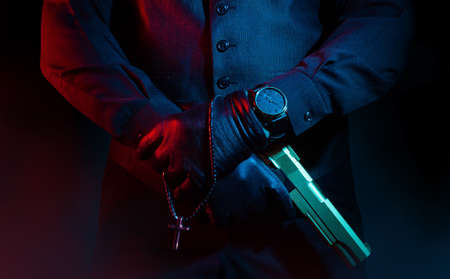 Photo of a male mafia criminal killer in suit and leather gloves holding a gun with cross on black background. Stockfoto