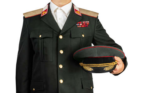 Isolated photo on white background of a military officer in uniform suit holding a peaked cap, torso view. Foto de archivo
