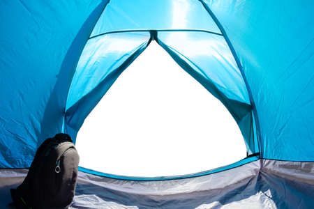 Photo of a white isolated copyspace from a blue camping tent door front view with travel backpack.