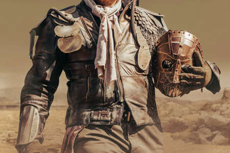 Photo of a post apocalyptic raider warrior torso in leather jacket with metal armor standing in wasteland with steel mask. Stockfoto