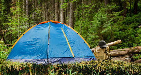 Photo of a camping tent with backpack and hat standing in daylight forest. Stockfoto