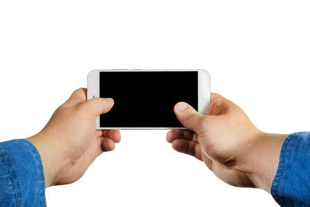Isolated first person view photo of a male hands in jeans shirt holding and playing a smartphone horizontally on white background.