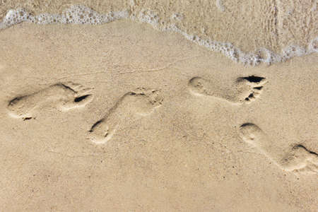 Photo of a sunny day sea shore footsteps printed on sand.