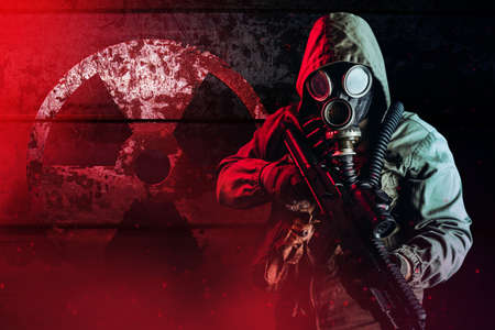 Photo of a post apocalyptic stalker soldier in gas mask and hood jacket holding rifle and standing on dark rusty metal wall with radiation sign and red glowing light. Stockfoto