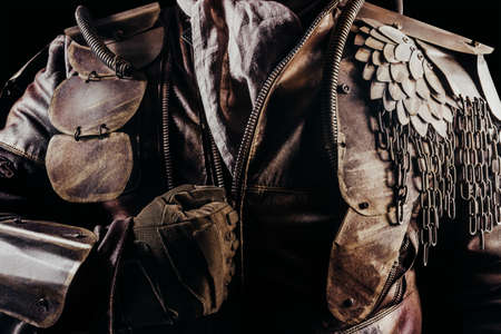 Photo of a post apocalyptic raider warrior putting on leather jacket with metal armor on black background.