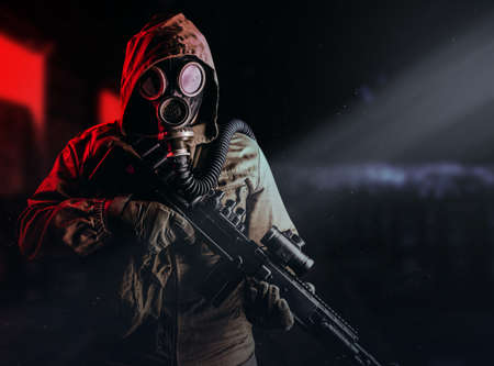 Photo of a post apocalyptic stalker soldier in gas mask and hood jacket holding rifle and standing on dark factory background with red light glow.