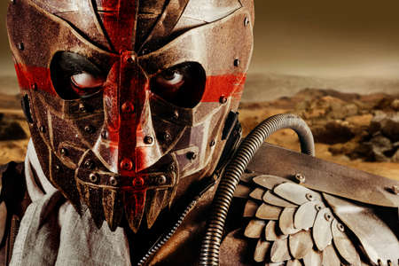 Photo of a post apocalyptic raider warrior in leather jacket with metal armor and steel mask with red cross painting standing in desert wasteland.