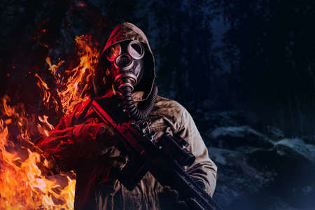 Photo of a post apocalyptic stalker soldier in gas mask and hood jacket holding rifle and standing and burning on dark night forest background. Stockfoto