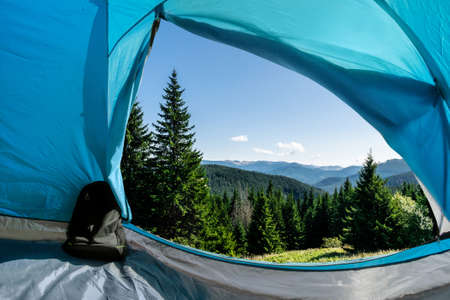 Photo of a sunny day mountain forest view from a blue camping tent door with travel backpack.