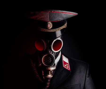 Portrait photo of a post apocalyptic military officer in uniform suit and peaked cap standing in soviet gas mask on black background.