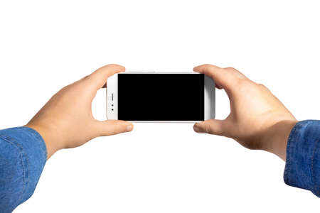 Isolated first person view photo of a male hands in jeans shirt holding a smartphone horizontally on white background.