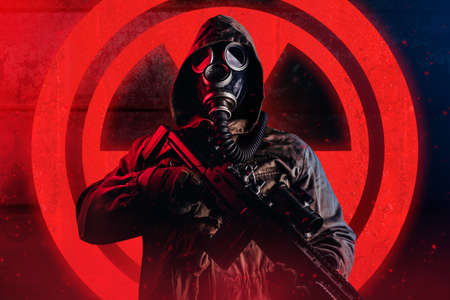 Photo of a post apocalyptic stalker soldier in gas mask and hood jacket holding rifle and standing on dark rusty metal wall with red glowing radiation sign.