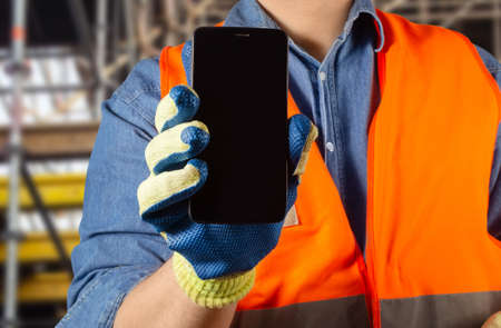 Photo of a male worker in orange jacket uniform and gloves holding a black smartphone.