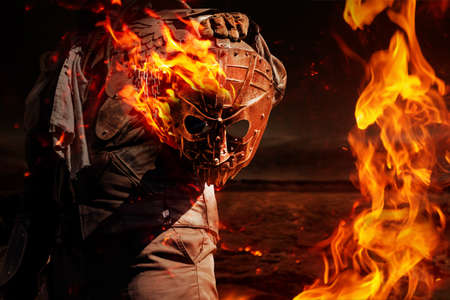 Photo of a post apocalyptic raider warrior in leather jacket with metal armor  standing in night wasteland and holding a burning metal mask.