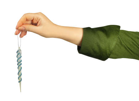 Isolated photo of a girl hand in green shirt holding christmas icicle decoration toy on white background.