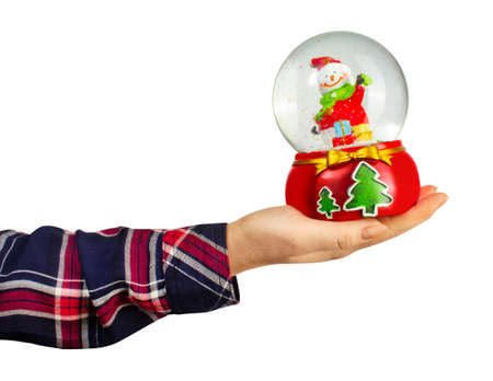 Isolated photo of a girl hand in shirt holding christmas decorative snowball toy on white background.