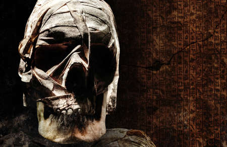Photo of an old andcient egyptian mummyfied human skull with bondages on dark crypt background.