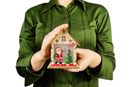 Isolated photo of a girl in green shirt holding a christmas wooden toy house decoration. Stock Photo