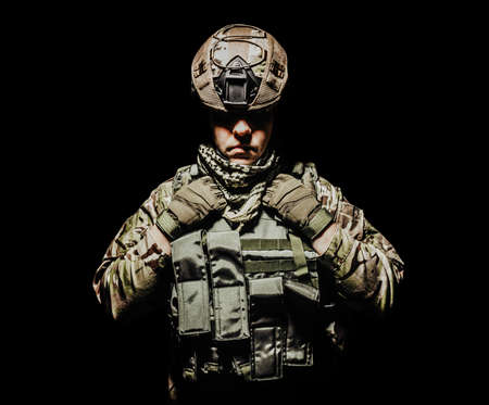 Photo of a fully equipped shaded soldier in armor vest and helmet standing on black background.
