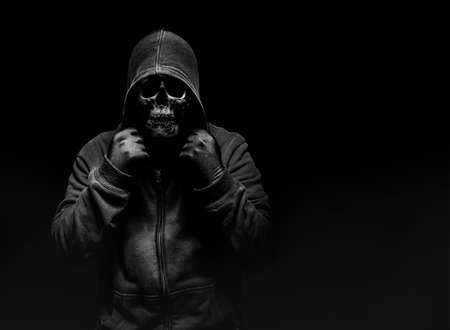 Horror photo of a scary man in hoodie with skull face on black background. Stockfoto - 162719229