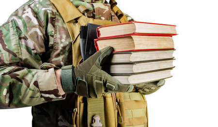 Isolated photo of a soldier in uniform holding stack of books on white background, side view. Stockfoto