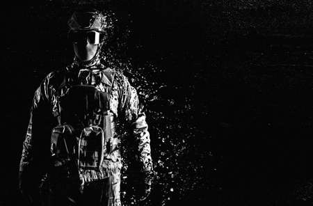 Black and white photo of a fully equipped soldier standing in tactical clothing and dissolving on grungy black background.