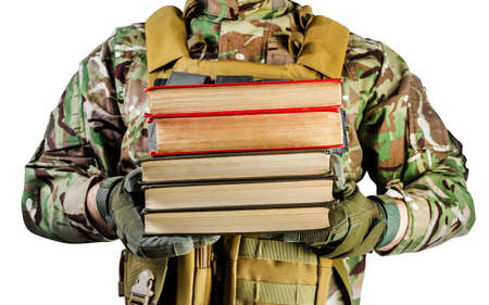 Isolated photo of a soldier in uniform holding stack of books on white background, front view.