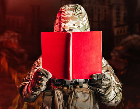 Photo of a soldier in uniform and armor helmet holding opened red book on ruined city background. Stockfoto
