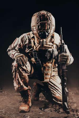 Photo of a fully equipped soldier in armored vest. helmet and camouflaged outfit kneeling with rifle on black background. 写真素材