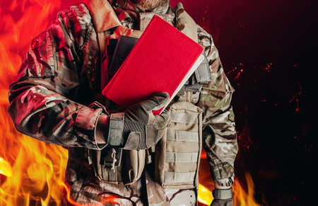 Photo of a soldier in uniform holding closed red book on burning flame background. Stockfoto