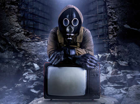 Photo of stalker soldier in jacket and armored vest and rubber gloves standing with old tv set on ruined dark background.