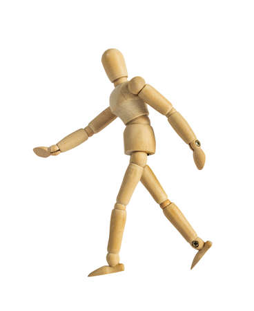 Isolated photo of a wooden dummy mannequin figurine walking side view on white background.