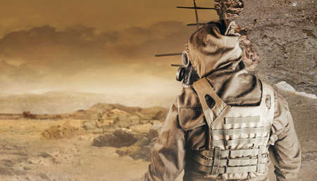 Photo of a stalker in jacket, armored vest standing back view in soviet gas mask with filter on destructed apocalyptic desert wasteland background. Stockfoto