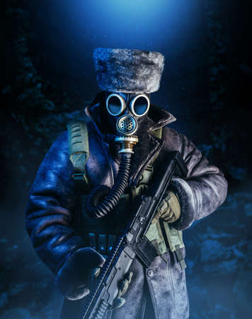 Photo of winter stalker soldier in fur coat, hat standing with pouch vest, gas soviet mask and rifle in stormy snowfall weather, full torso view.